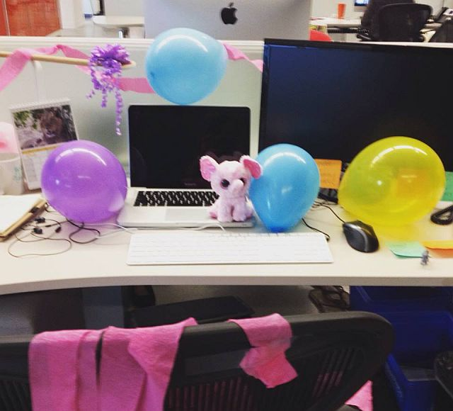 Desk at work covered in balloons and streamers