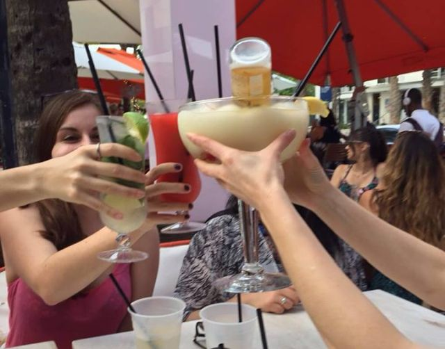 All girls holding up cocktails to cheers in Miami