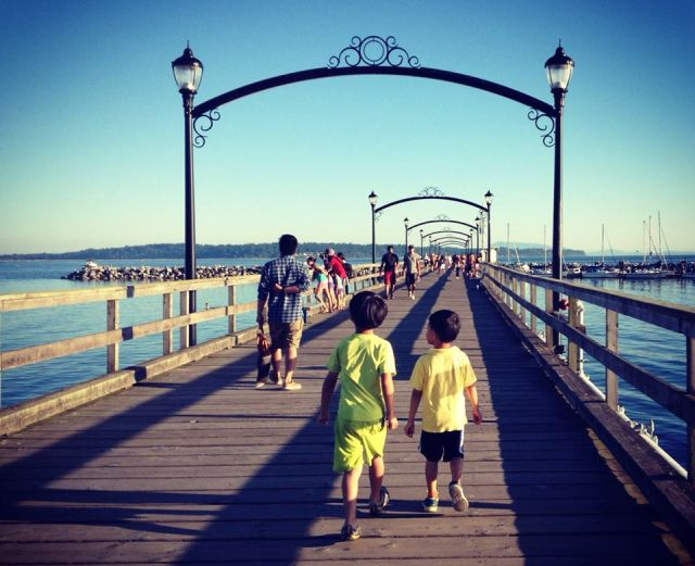 Two small children walking along the boardrock in Whiterock, British Columbia