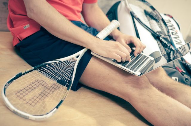 Man working on laptop while holding tennis racket
